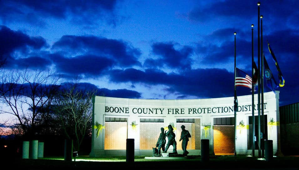 At the Boone County Fire Protection District Headquarters, a precast concrete semi-circular wall acts as a backdrop for a sculpture from the statue side and a view-framing portal element from the building side. Photograph by Adam Wisneski.